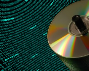 Stack of CD/DVD disks against a curved field of binary code
